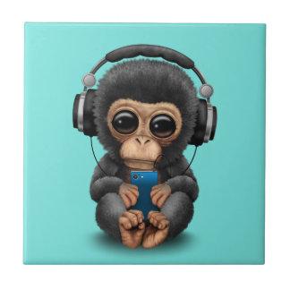 ヘッドホーンおよび携帯電話を持つベビーのチンパンジー タイル