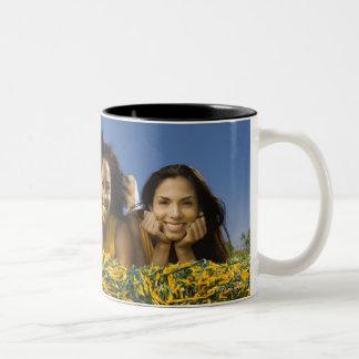 ポンポンを持つ草にあっているメスのチアリーダー ツートーンマグカップ
