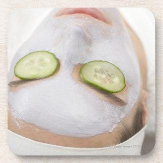 マスクおよびきゅうりの切れを持つ女性 コースター