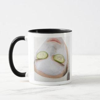 マスクおよびきゅうりの切れを持つ女性 マグカップ