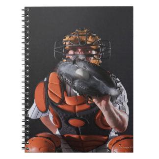 ミットの球を握る野球のキャッチャー ノートブック
