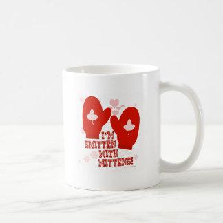 ミトンによって強打される コーヒーマグカップ