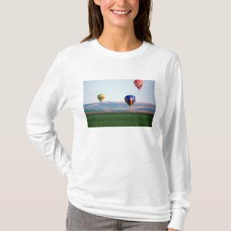 ムギ上のカラフルな熱気の気球の浮遊物 Tシャツ