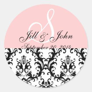 モノグラムは日付のダマスク織のピンクの結婚式のステッカーを示します ラウンドシール