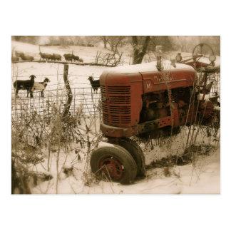 ヤギのクリスマスの郵便はがきが付いている古く赤いトラクター ポストカード