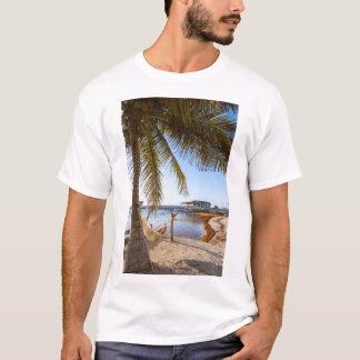 ヤシの木、ベリセの下でハンモックでリラックスしている人 Tシャツ