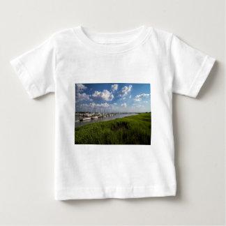 ヨットのマリーナおよび緑豊かな緑の牧草地 ベビーTシャツ