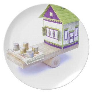 ヨーロッパの硬貨およびノートの山が付いているバランスの家 プレート
