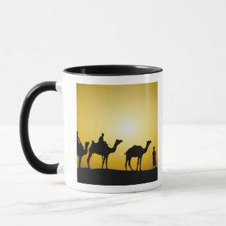 ラクダおよび日没でシルエットを描かれるラクダの運転者 マグカップ