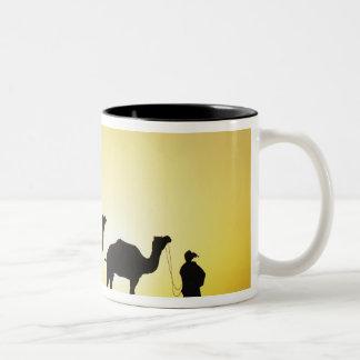 ラクダおよび日没、2でシルエットを描かれるラクダの運転者 ツートーンマグカップ