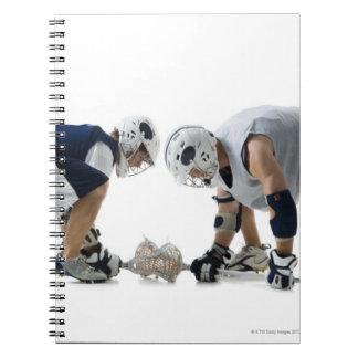 ラクロスを遊んでいる2人の若者のプロフィール ノートブック