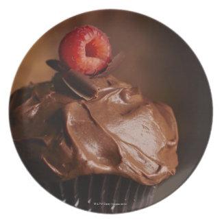 ラズベリーのトッピングが付いているチョコレートカップケーキ プレート