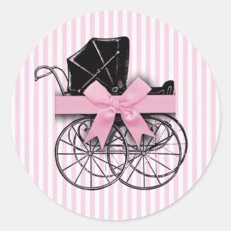 リボンが付いているピンクのヴィンテージの乳母車の手押車 ラウンドシール