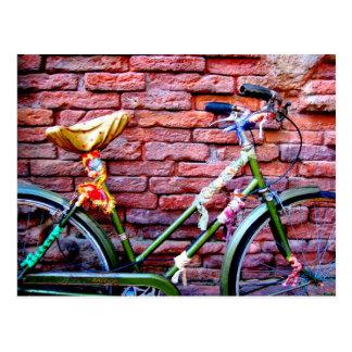 レンガ壁に対して傾く緑の自転車 ポストカード