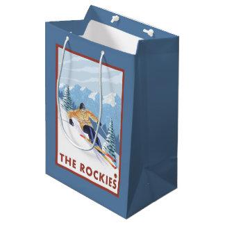 ロッキー山脈- Downhhillの雪のスキーヤー ミディアムペーパーバッグ