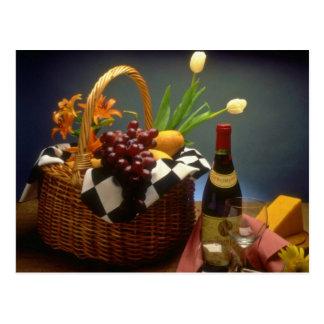 ワイン、チーズ、パンが付いている黄色いピクニックバスケット ポストカード