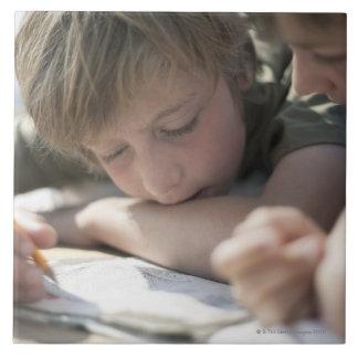 一緒に書いている2人の男の子 タイル