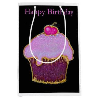 上のおいしいさくらんぼが付いているピンクのカップケーキ ミディアムペーパーバッグ