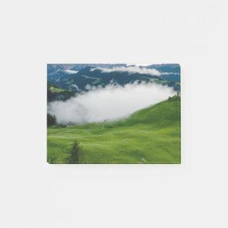 下雲が付いている完全な緑山の上 ポストイット