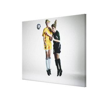 中間空気ヘッディングの2人のメスのサッカーの選手 キャンバスプリント