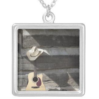 丸太小屋で傾くギターのカーボーイ・ハット シルバープレートネックレス