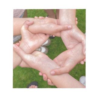 互いを保持している女の子の手を搭載する腕 ノートパッド