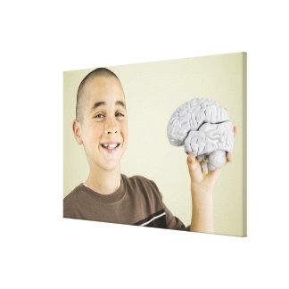 人間の脳モデルを握っている男の子 キャンバスプリント