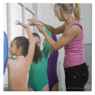 体操のクラスで伸びている女の子 タイル