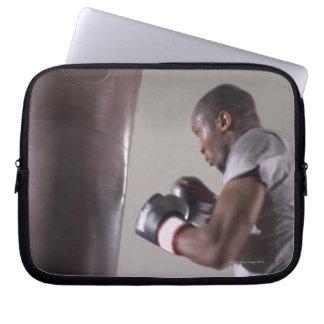 体育館でサンドバッグを使用しているボクサー ラップトップスリーブ