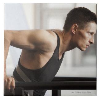 体育館で体操装置を使用しているオスのアスリート タイル