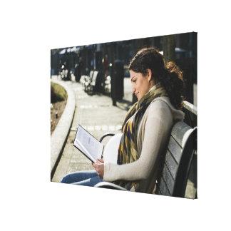 公園の妊娠した中東の女性の読書 キャンバスプリント