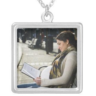 公園の妊娠した中東の女性の読書 シルバープレートネックレス