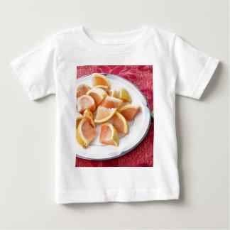 円形のプレートの赤いグレープフルーツの部分 ベビーTシャツ