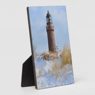 冬の岩が多い海岸の丈夫な灯台 フォトプラーク