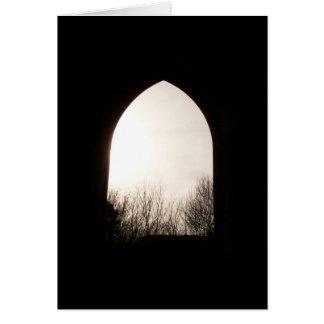 冬の木が付いている古いアーチの窓、 カード