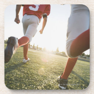 分野で走っているフットボール選手 コースター