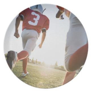分野で走っているフットボール選手 プレート