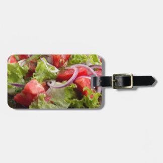 切り刻まれたトマトの切れのサラダが付いているクローズアップのプレート ラゲッジタグ