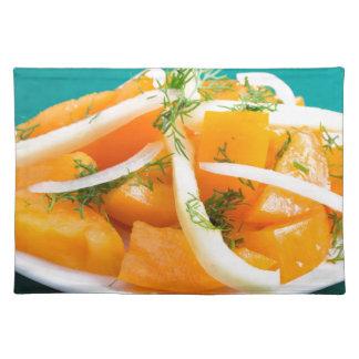 切れのタマネギが付いているプレートのオレンジトマト ランチョンマット