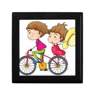 動きが速いバイクの女の子そして男の子の乗馬 ギフトボックス
