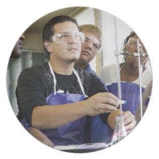 化学実験室で実験を行っている学生 プレート