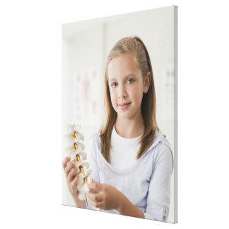 医者のオフィスの脊柱のモデルを握っている女の子 キャンバスプリント