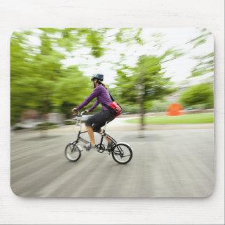 取り替えるのに折るバイクを使用している女性 マウスパッド