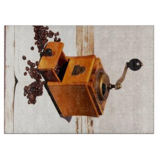古いコーヒー製造所およびコーヒーの豆 カッティングボード