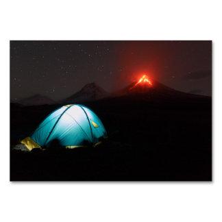 噴火の火山の背景のツーリストのテント