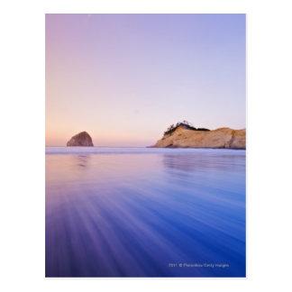 夜明けによってぼやけられる青い紫色の波の三角波の石 ポストカード