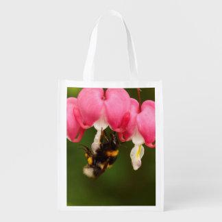 大げさに同情する人の花の買い物袋ののまわりに エコバッグ