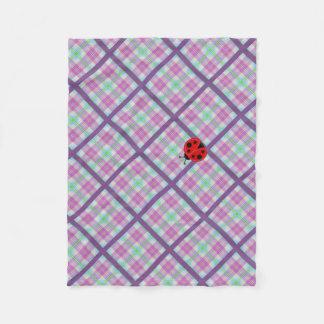 女性が付いているBugピンクおよび紫色の格子縞 フリースブランケット