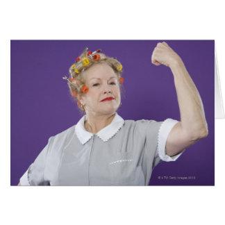 女性の腕を緊張させるヘア・カーラーを身に着けている押し進みます、 カード
