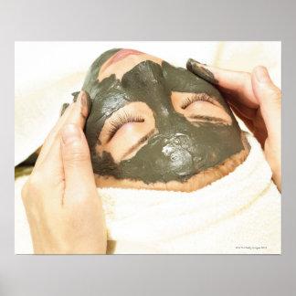 女性の顔の泥パックを摩擦するエステティシャン、 ポスター